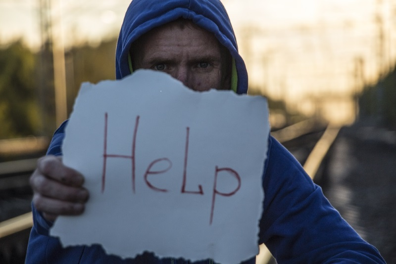 man in hoodie holding a hand written help sign