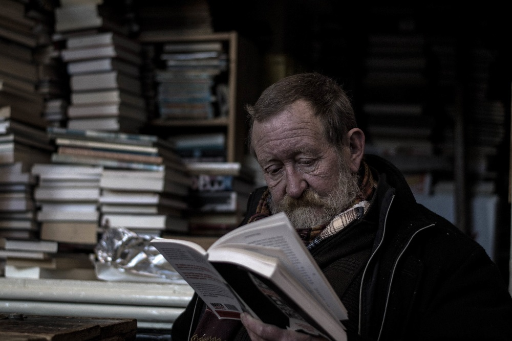 old man reading a book in a library